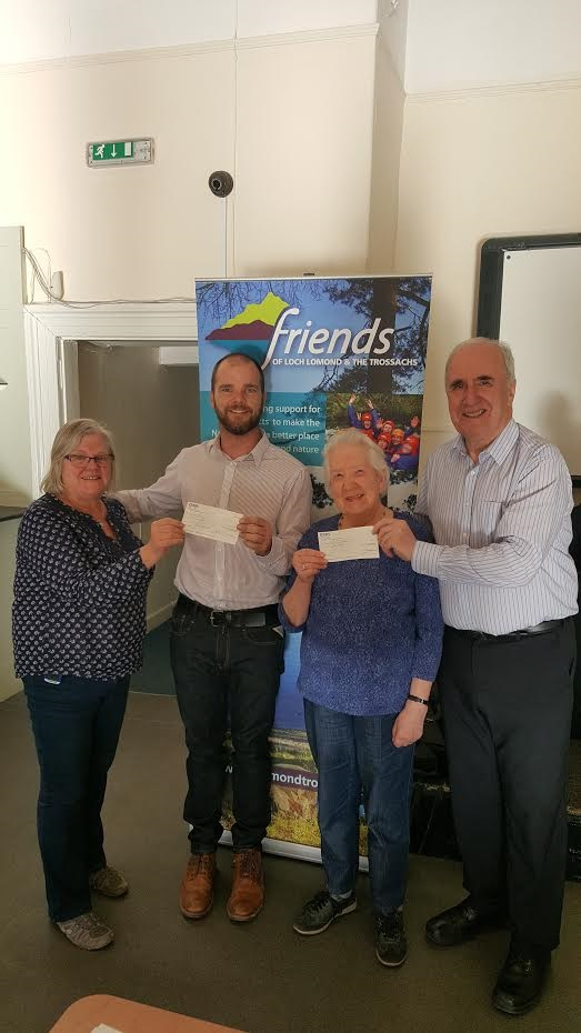 Friends Trustee and Callander Community Development Trust Town Co-ordinator Sheila Winstone (left) presents a cheque to Wayne Johnson of Trossachs Mobility (second left), while Callander Community Development Trust Secretary Anne Docherty (second right) receives a cheque from James Fraser, Chairman of the Friends (right).