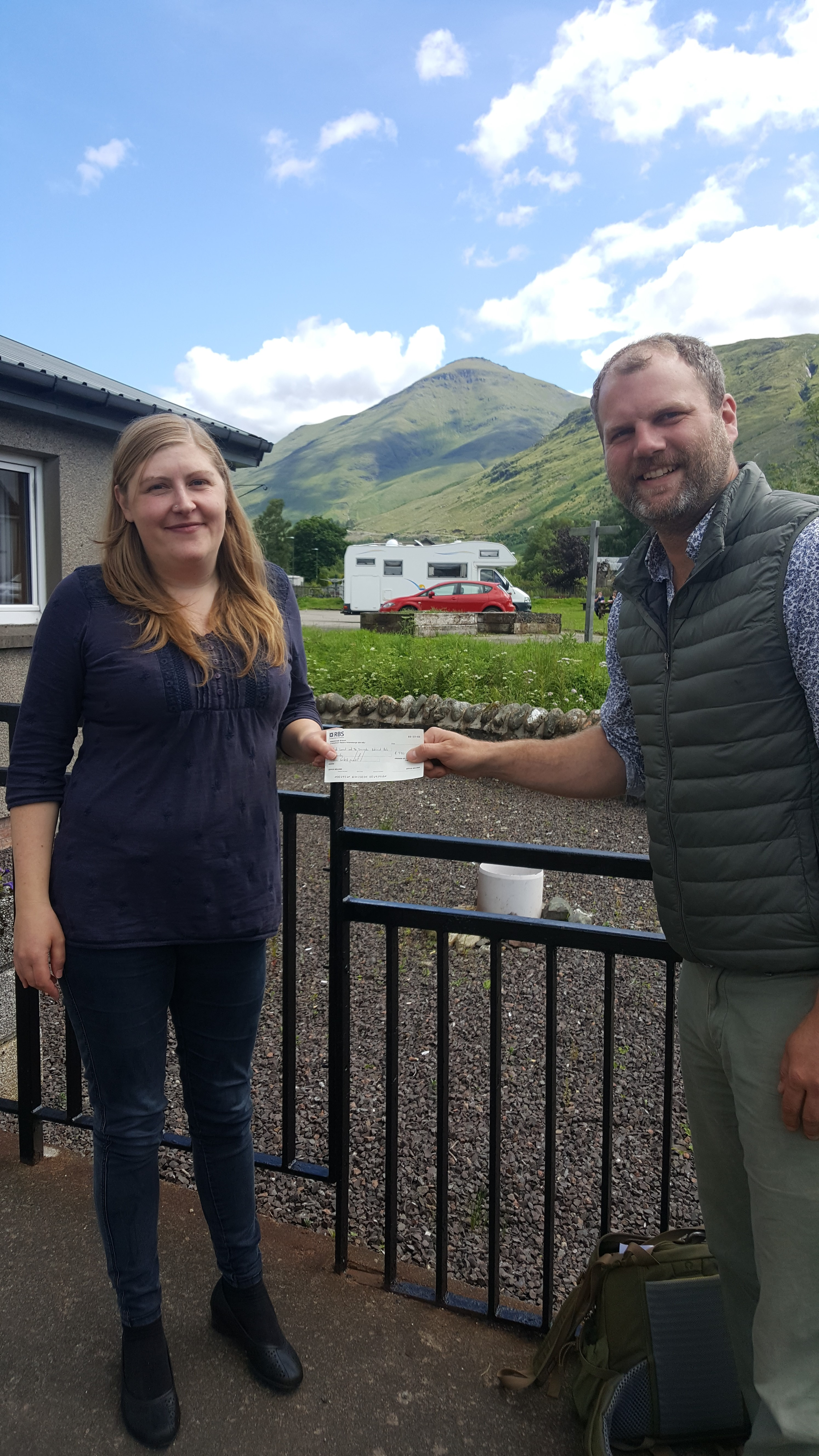 Jared Bowers, Project Officer of Friends of Loch Lomond and The Trossachs, presents the cheque for £500 to Kelly Clapperton-Bates of Strathfillan Community Development Trust.